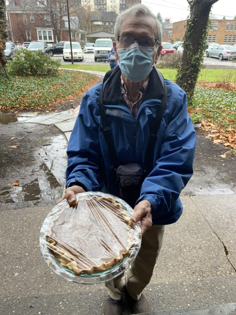 volunteer in mask delivering pie