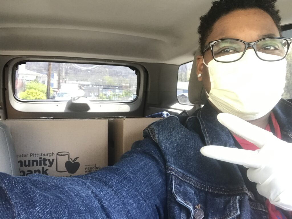 Lachelle E with mask on in a car with food bank boxes in backseat