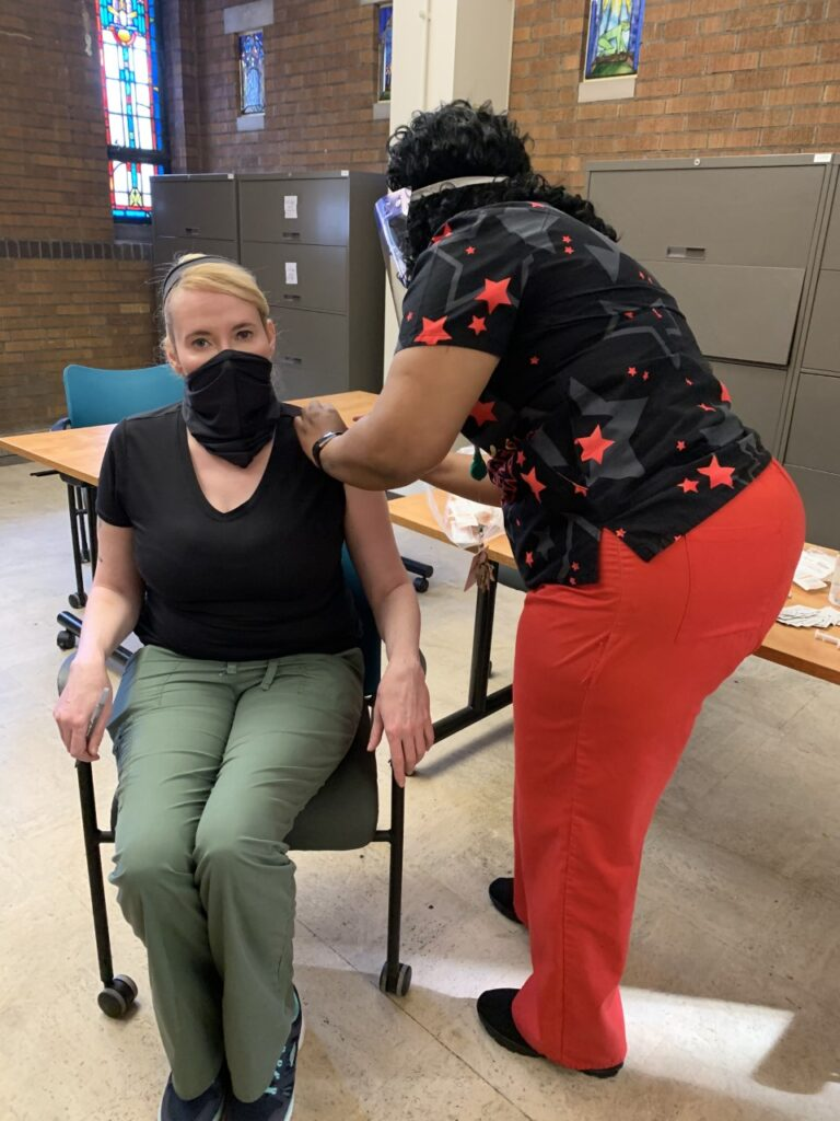 Woman seated in chair wearing surgical mask receives a shot from healthcare provider