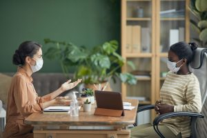 two women talking across a desk while wearing medical masks